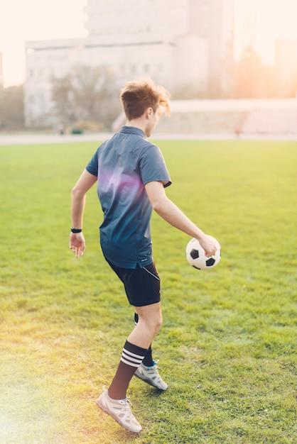 匿名の男がボールを蹴る 無料写真