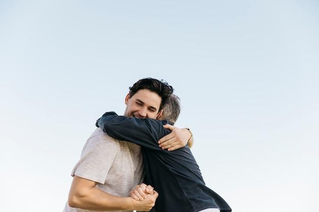 空の背景に抱擁する父と息子 無料写真