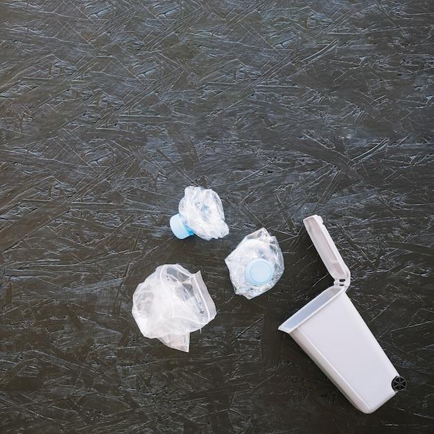 小型ゴミ箱の近くに詰まったプラスチック水ボトルの高さ 無料写真