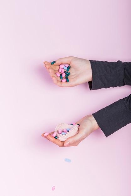 ピンクの背景にキャスト歯科模型の石膏に注ぐ人間の手 無料写真