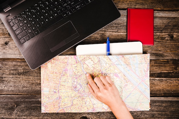 Рука путешественника, указывающая на местоположение на карте Бесплатные Фотографии