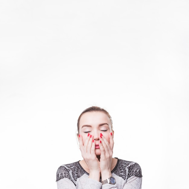 Женщина с закрытыми глазами, касаясь ее птенцов двумя руками на белом фоне Бесплатные Фотографии