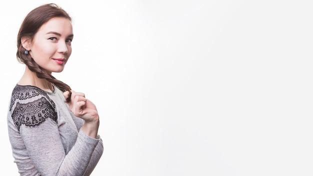 白い背景に彼女の編組を保持している美しい若い女性 無料写真