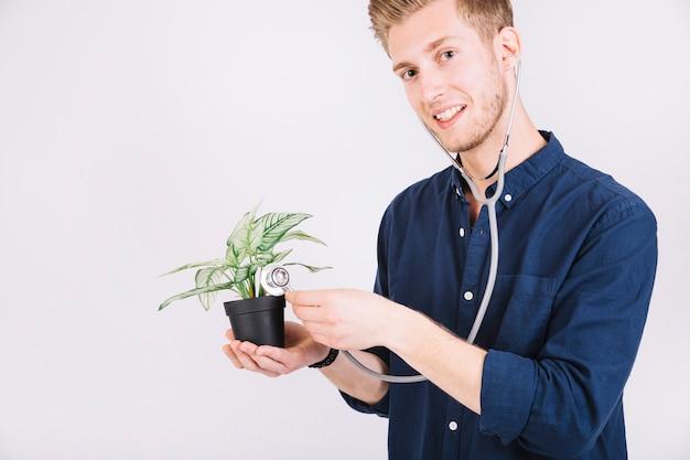 Человек, изучающий растение в горшках с помощью стетоскопа Бесплатные Фотографии