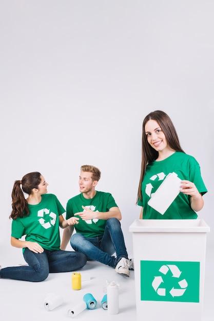 幸せな女の子、リサイクルアイコンとゴミ箱にボトルを投げて 無料写真