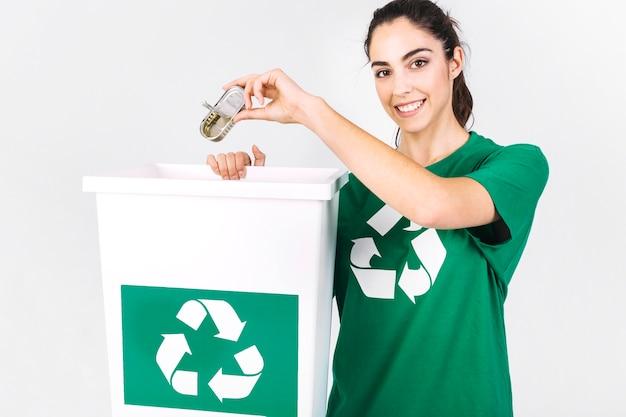 リサイクルゴミ箱でミニティフィンボックスを投げる幸せな若い女性 無料写真