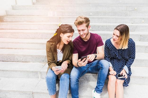携帯電話の画面を見て階段に座っている友人のグループ 無料写真