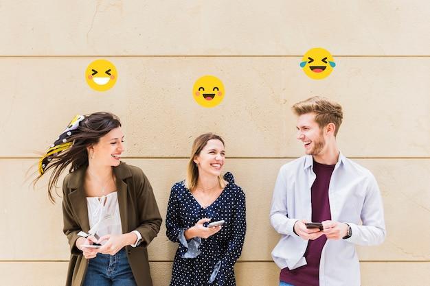 携帯電話で笑顔の絵文字を共有する幸せな友人のグループ 無料写真