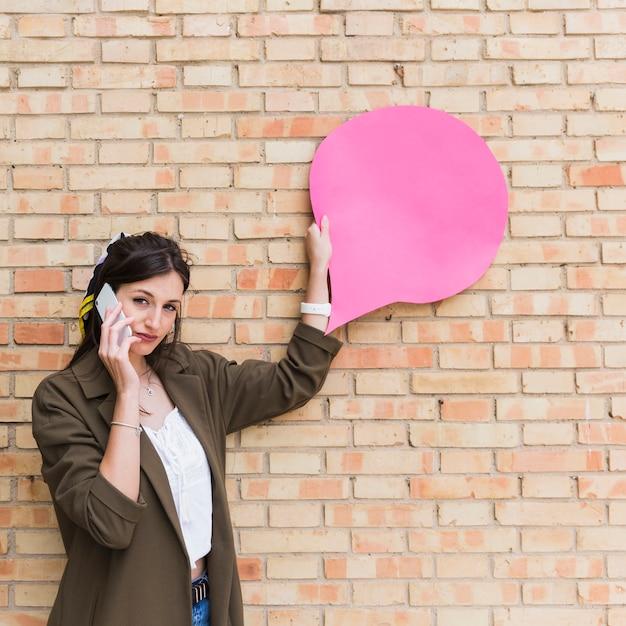 Молодая женщина, используя сотовый телефон, проведение розовый пустой речи пузырь бумаги на кирпичной стене Бесплатные Фотографии