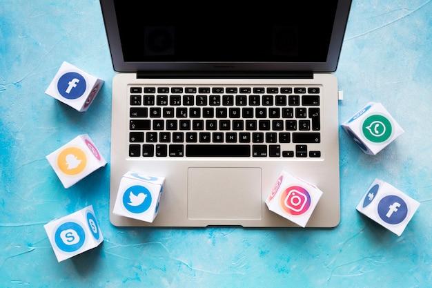 青い背景の上にノートパソコンのソーシャルメディアのアイコンブロック 無料写真