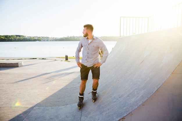 Молодой человек катается на роликах в скейт-парке в солнечный день Бесплатные Фотографии