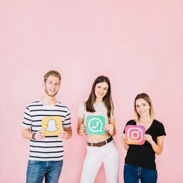 様々なソーシャルメディアのアイコンを持つ幸せな友人のグループ 無料写真