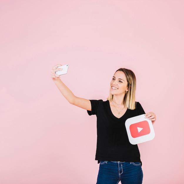 携帯電話からセルフリーを取って遊ぶアイコンを持つ幸せな女性 無料写真