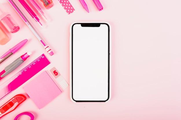 女性のピンクのキットの文房具とスマートフォン 無料写真