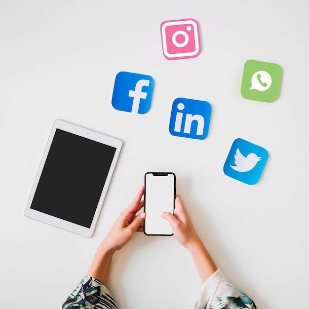人間の手は、デジタルタブレットと鮮やかなソーシャルメディアのアイコンの近くに携帯電話を保持 無料写真