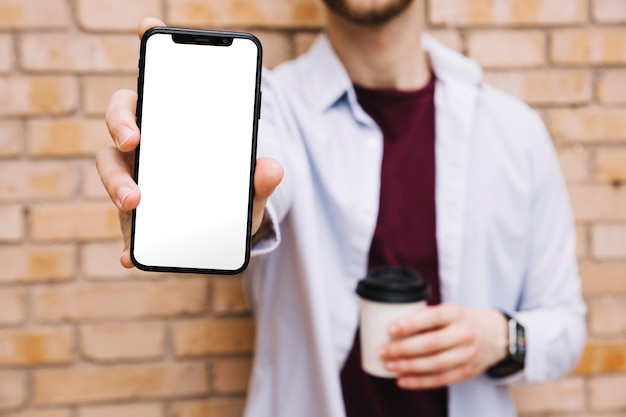 空の白い画面でスマートフォンを示す男の手のクローズアップ 無料写真