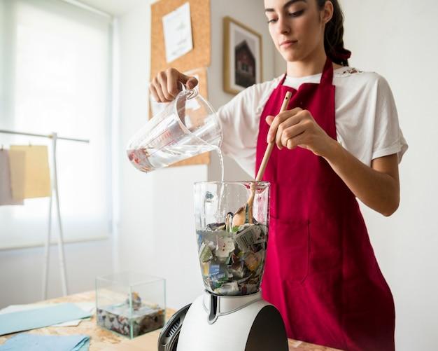 紙を粉砕しながらミキサーで水を注ぐ女性 無料写真