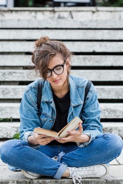 Молодая женщина, читающая книгу на лестнице Бесплатные Фотографии