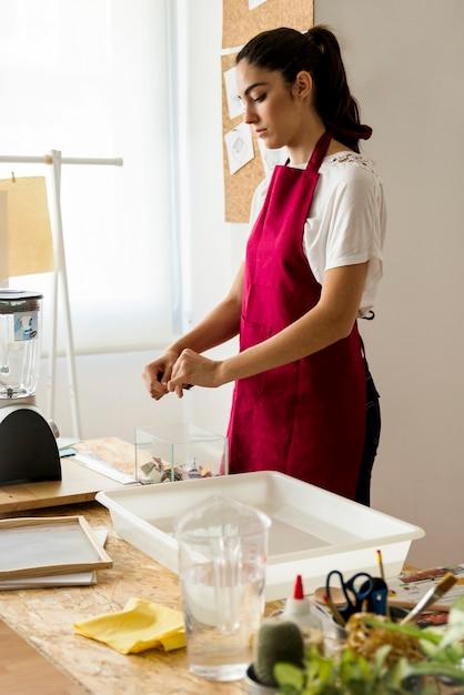トレイの近くのガラス容器の上に紙を引き裂く女性 無料写真