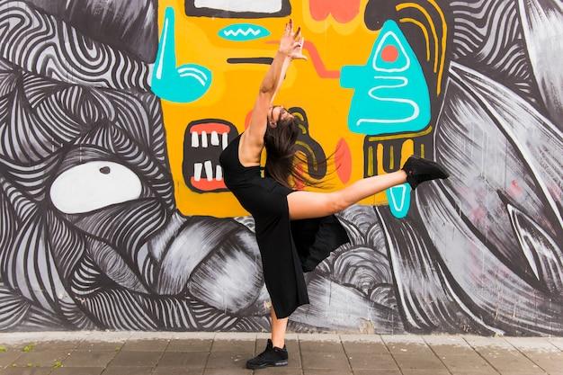 Активная молодая женщина танцует против стены граффити Бесплатные Фотографии