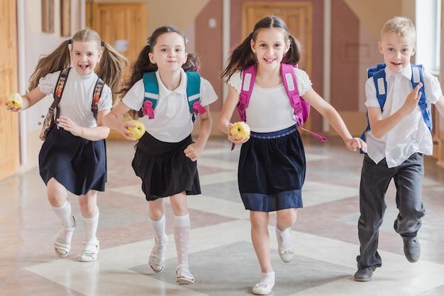 学校の廊下を走っているリンゴを持つ子供たち 無料写真