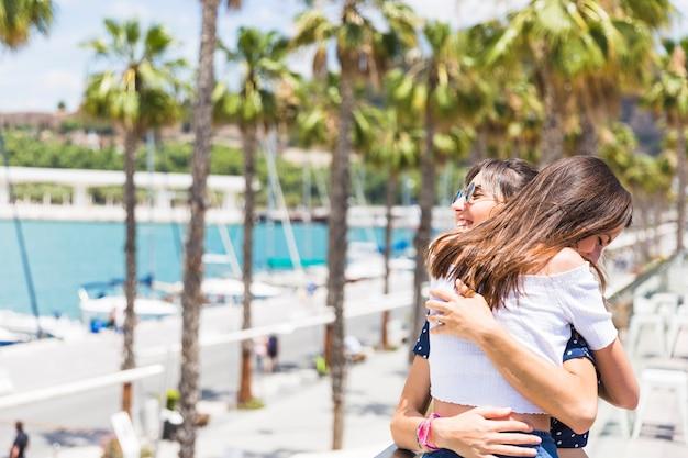 Счастливые подруги обниматься на набережной Бесплатные Фотографии