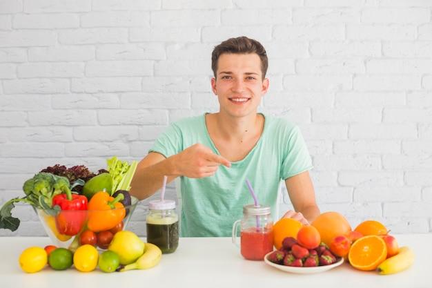 テーブル、新鮮な果物の方に指を指す男 無料写真