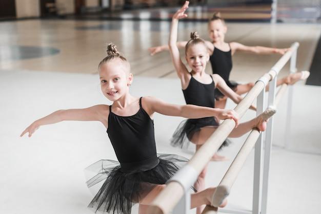 バレエの足を伸ばす笑顔のバレリーナの女の子 無料写真
