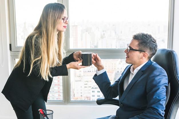 オフィスで彼女の上司にコーヒーを与えるビジネスマン 無料写真