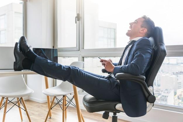 モバイルを使って職場で椅子に座っているハッピービジネスマン 無料写真