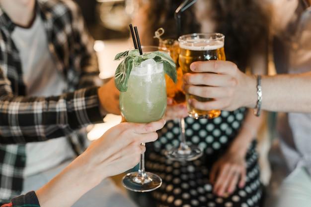さまざまなタイプの飲み物をトーストする友人のクローズアップ 無料写真