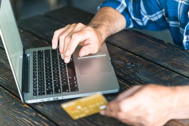 Рука человека с кредитной карточкой, набрав на ноутбуке над деревянным столом Бесплатные Фотографии