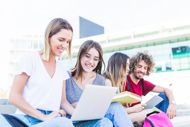 ストリートで勉強している陽気な学生 無料写真