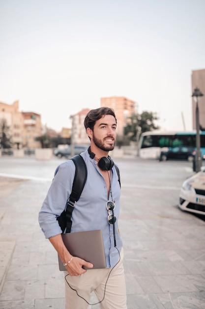 舗装の上で歩くラップトップと幸せな男性の観光客 無料写真