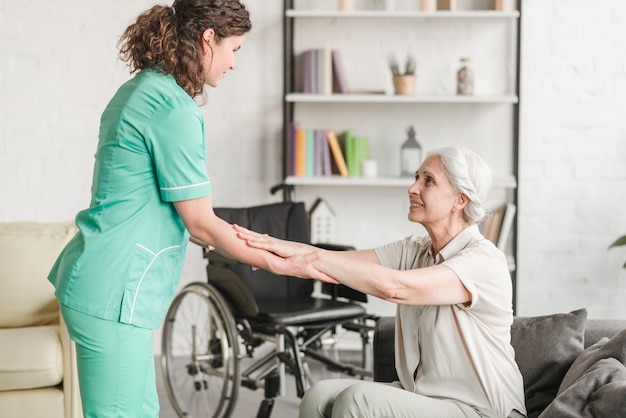 Женщина-медсестра, держащая за руки старшая женщина-инвалид Бесплатные Фотографии