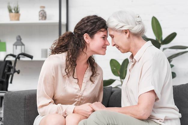 Мать и дочь, касаясь головы, держа друг друга за руку Бесплатные Фотографии