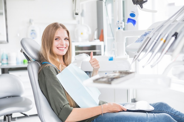 幸せな若い女性の患者は、歯の椅子の身に着けている確認のサインに座って 無料写真