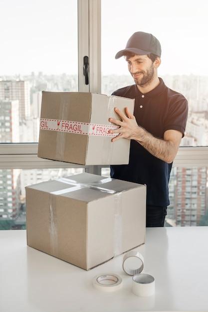 荷物を持っている笑顔の配達人 無料写真
