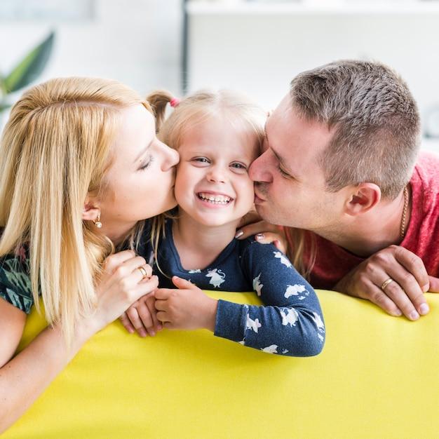 小さな娘にキスをする両親 無料写真