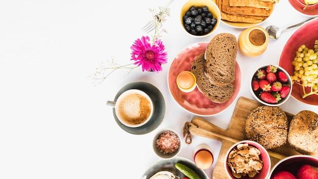 白い背景に果物やお茶と健康的な朝の朝食 無料写真