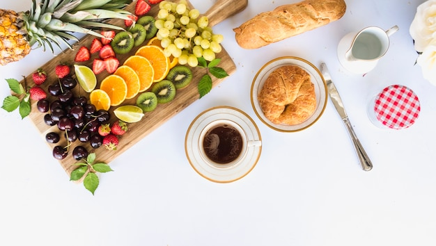 フルーツ盛り合わせ、紅茶、パンを使った健康的な朝食のオーバーヘッドビュー 無料写真