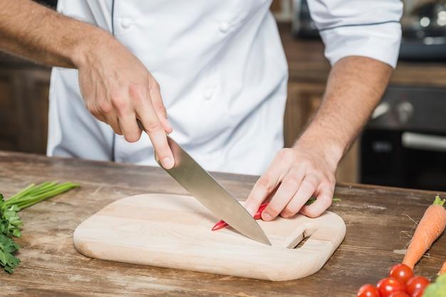 シェフの手は、赤い唐辛子を切り刻んでボードを切る 無料写真