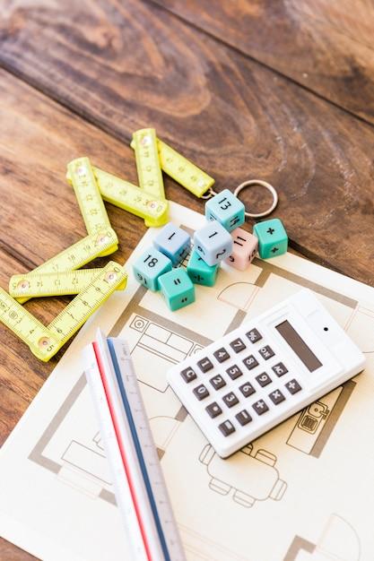 メジャーテープ、定規、電卓、数学ブロック、および青写真の高さのビュー 無料写真