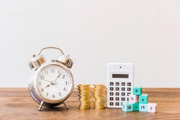 木製の机の上に目覚まし時計、積み重ねられたコイン、計算機および数学のブロック 無料写真