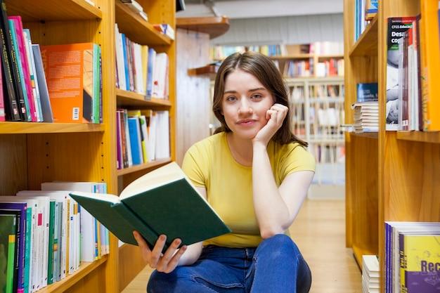 ブックシェルフの間をカメラで見ている本を持つティーン・ガール 無料写真