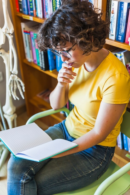 ライブラリに座って読書している思慮深い女性 無料写真