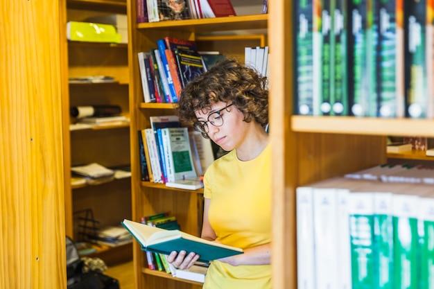 書棚の後ろに立っている女性を勉強する 無料写真