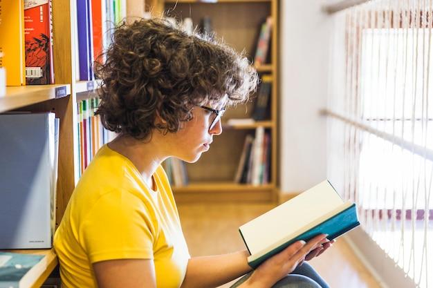 本棚に傾いている床に座っている女性 無料写真