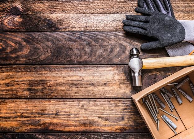 木製の背景に手袋、ハンマー、釘、壁のプラグの高さのビュー 無料写真