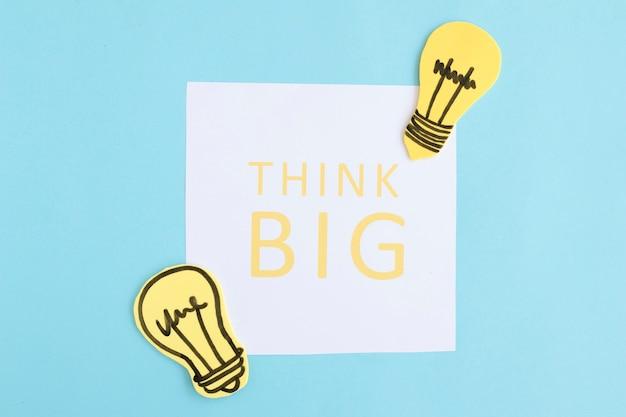 青い背景に電球と白い紙に大きなテキストを考える 無料写真